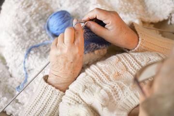 Senior woman knitting warm sock, closeup