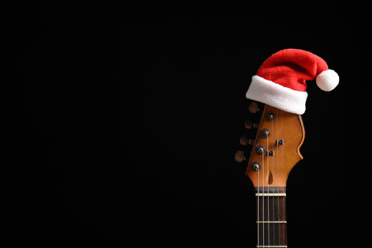Guitar with Santa hat on black background. Christmas music concept