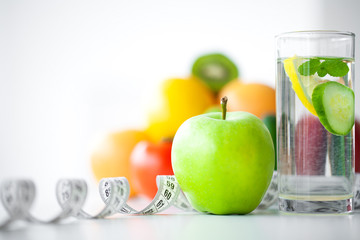 Green apples, glass water with mint leaves, lemon and cucumber, tape measure - concept of healthy eating and modern lifestyle