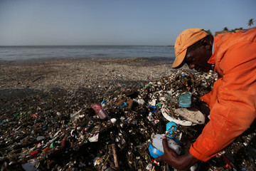 A worker from the MOPC removes plastic and other debris during a cleanup on the shores of Montesinos beach, in Santo Domingo