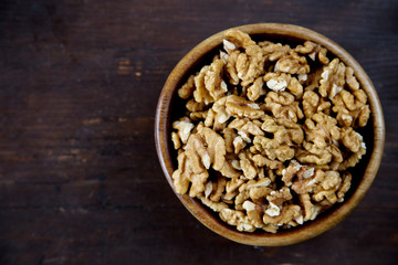 A wooden bowl of walnuts on a dark wooden background top view