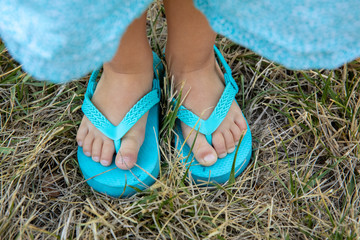 A Little Girl's Feet in Turquoise Flip Flops With R and L printed on the Toes