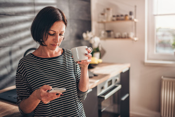 Woman standing in the kitchen and using smart phone
