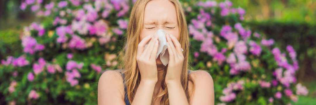 BANNER Pollen allergy concept. Young woman is going to sneeze. Flowering trees in background long format