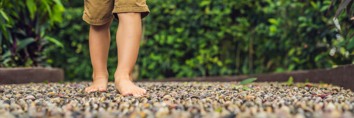 Boy Walking On A Textured Cobble Pavement, Reflexology. Pebble stones on the pavement for foot reflexology BANNER long format
