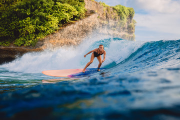 Surfgirl ride at surfboard on ocean wave. Woman in ocean during surfing.