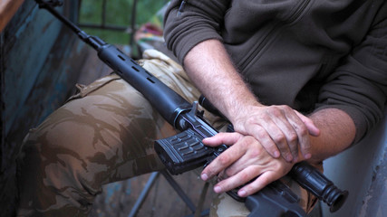 soldier hands and Sniper rifle close up. war.