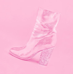 Stylish pink women's leather shoe with heel made of confetti on pastel background.