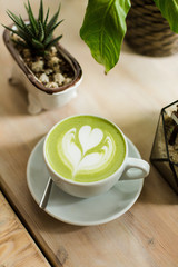 Green tea matcha latte art with succulent  cropped at an angle at a coffee shop cafe on wooden table