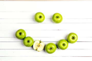 Smiling face of green apples on white wooden table. Apple emoticon. T
