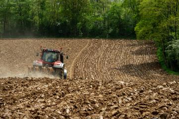 Farmer on tractor plow field, France Wall mural