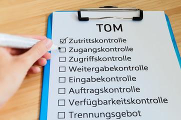 Schild mit der Aufschrift TOM'S (Technisch organisatorische Maßnahmen) in Englisch Technically organizational measures mit einer Tafel und Block zur Signalisierung typischer Tätigkeiten von Datenschut