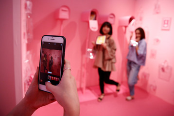 Visitors pose for pictures with an art installation at Vinyl Museum in Tokyo