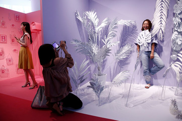 A visitor poses for pictures with an art installation at Vinyl Museum in Tokyo
