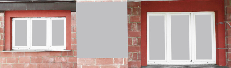 panoramic photo.an empty poster between the Windows of the house