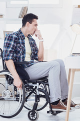 Need inspiration. Handsome man turning head while sitting on his wheelchair