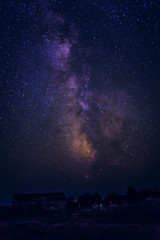 The Milky Way and stars in the night sky over the house and trees.