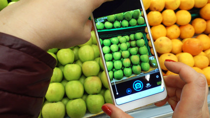 Woman's Hand taking picture of fresh apples and other fruits using smart phone at grocery store.