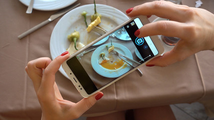 The process of photographing a smartphone. The girl is making a photo for the social network. Plates with the remains of food. Breakfast at the Turkish hotel.