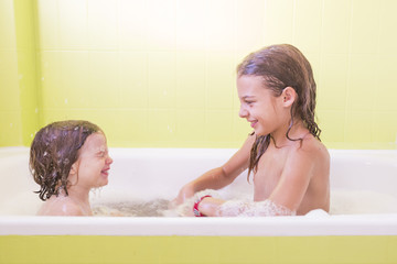 Happy laughing sister kids taking a bath playing with foam bubbles. Little children in a bathtub. Family lifestyle indoors
