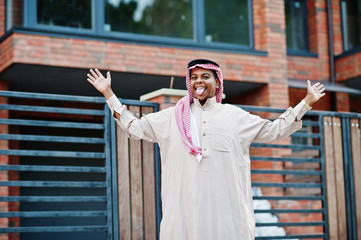 Middle Eastern arab man posed on street against modern building shows tongue.