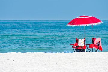 Beach umbrella, chairs, white sand and aquamarine water