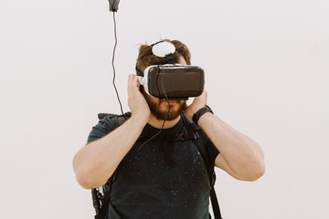 Man wearing glasses of virtual reality in white room