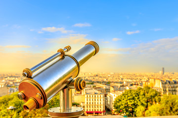 Closeup of look-out binoculars with view above urban cityscape skyline of Paris at sunset light from terrace of Cathedral Sacre Coeur, the highest city point of Paris, Montmartre, France. Copy space.