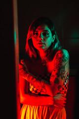 Tattooed woman in red light