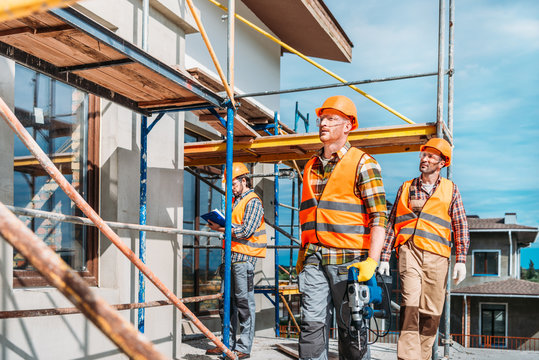 group of handsome builders working together at construction site