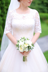 aucasian young bride keeping bouquet of flowers and wearing white dress with veil. Concept of wedding photo session.