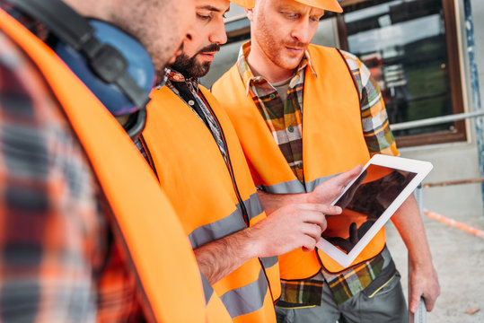 close-up shot of group of builders using digital tablet at construction site