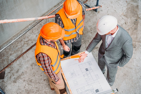 high angle view of builders and architect discussing blueprint at construction site