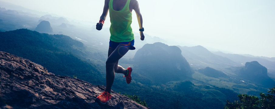 woman running on mountain top cliff edge