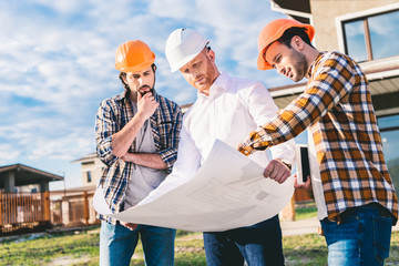 group of handsome architects with blueprint in garden at construction site