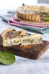 homemade pie with spinach and cheese, on a white wooden background. serving of pie
