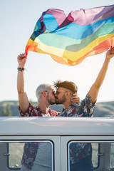 Kissing gay couple holding LGBT flag