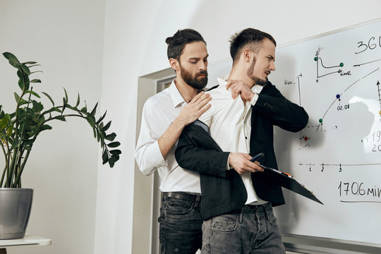 Sexual harassment and abuse at work. A male boss assaulting a male employee from behind, trying to undress him. The subordinate rejecting unwanted touching, the expression of disgust on his face.