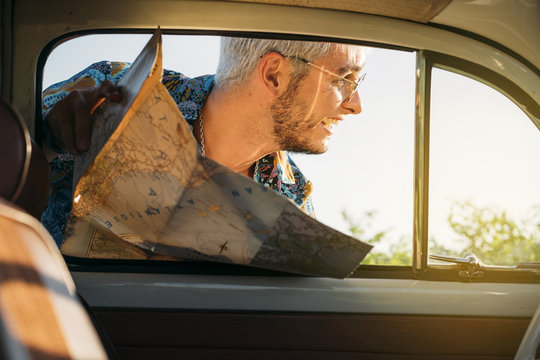 Cheerful man with map looking outside a car