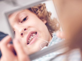 Boy looking in mirror extracting tooth
