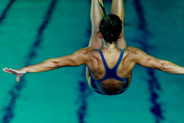 Foto op Canvas Duiken Female diver jumping into the pool