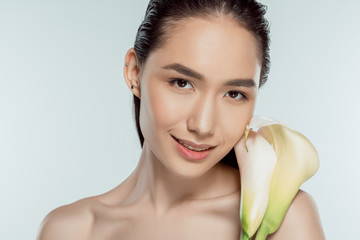 beautiful smiling asian girl with calla flower, isolated on grey