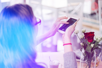 Girl makes a photograph of the flowers with her smartphone, light toning