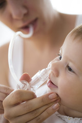 mother cleaning babies nose. nasal aspiration cleaner