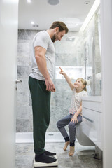 Father and daughter checking weight on bathroom scales