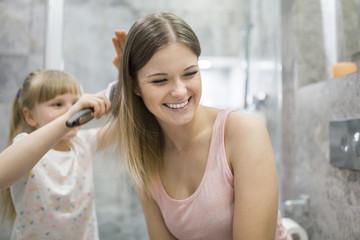 Little girl brushing her mother's hair