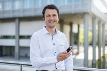 Portrait of smiling businessman with cell phone in the city