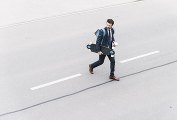 Businessman with takeaway coffee and skateboard walking on the street