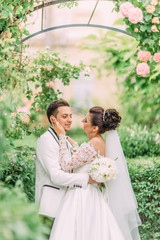 Sensitive outdoor portrait of the bride touching the face of the groom under the rose arch in the garden.