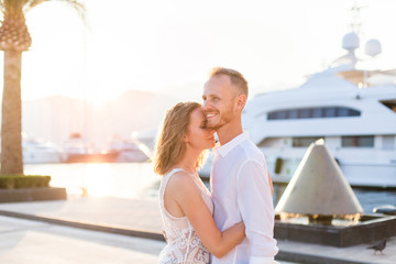 Couple of travelers are hugging in sea resort near yachts during romantic honeymoon vacation at sunset after wedding. Man and woman are happy tourists. Lovers are wearing in white clothes outdoor.